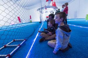 Le public de l'événément Game of Drones du LUDyLAB composé d'adultes et d'enfants dans la volière du Drone Indoor observant les drones voler en toute sécurité sous les filets de protection